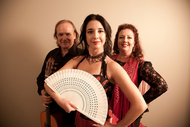 photograph of 3 people in dance costume. Woman in front with white fan