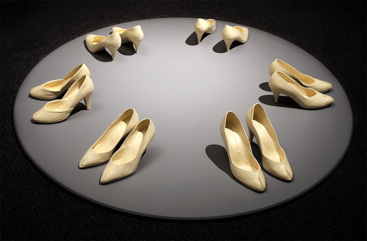 Six pairs of white high-heeled shoes arranged in a circle on a light grey circular base.