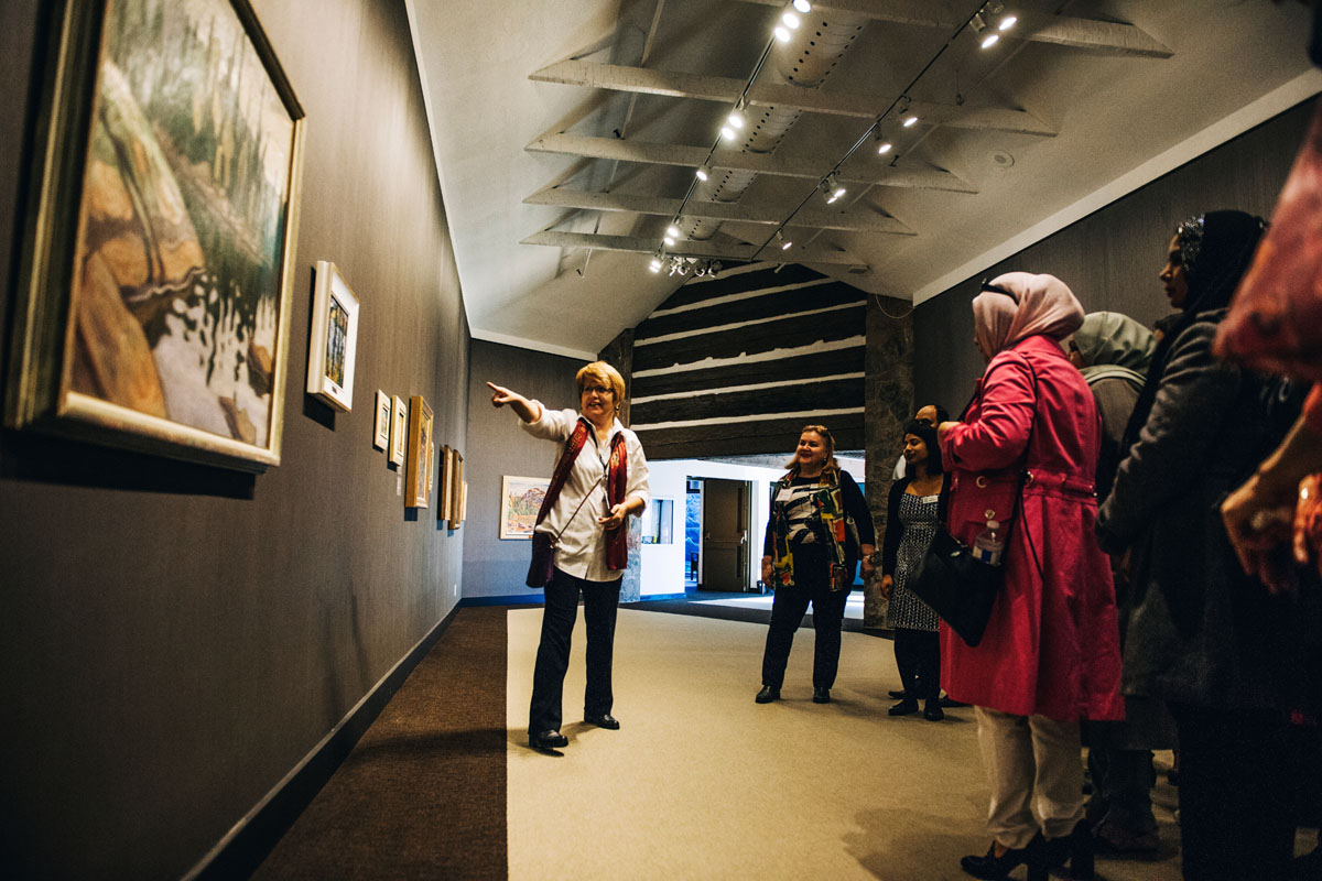 photograph of woman poiting to art in gallery with people gathered around her