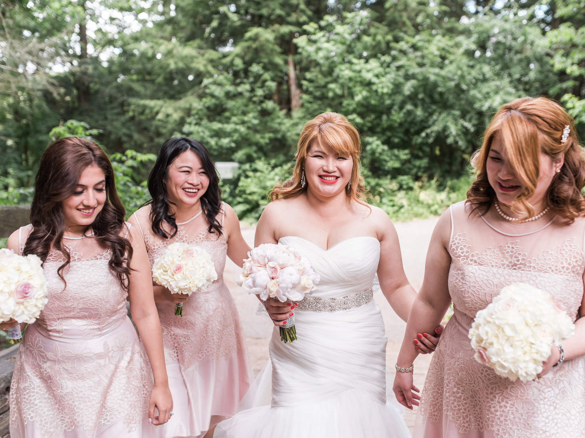 photograph of a bride and three adult bridesmaids in a woodland setting