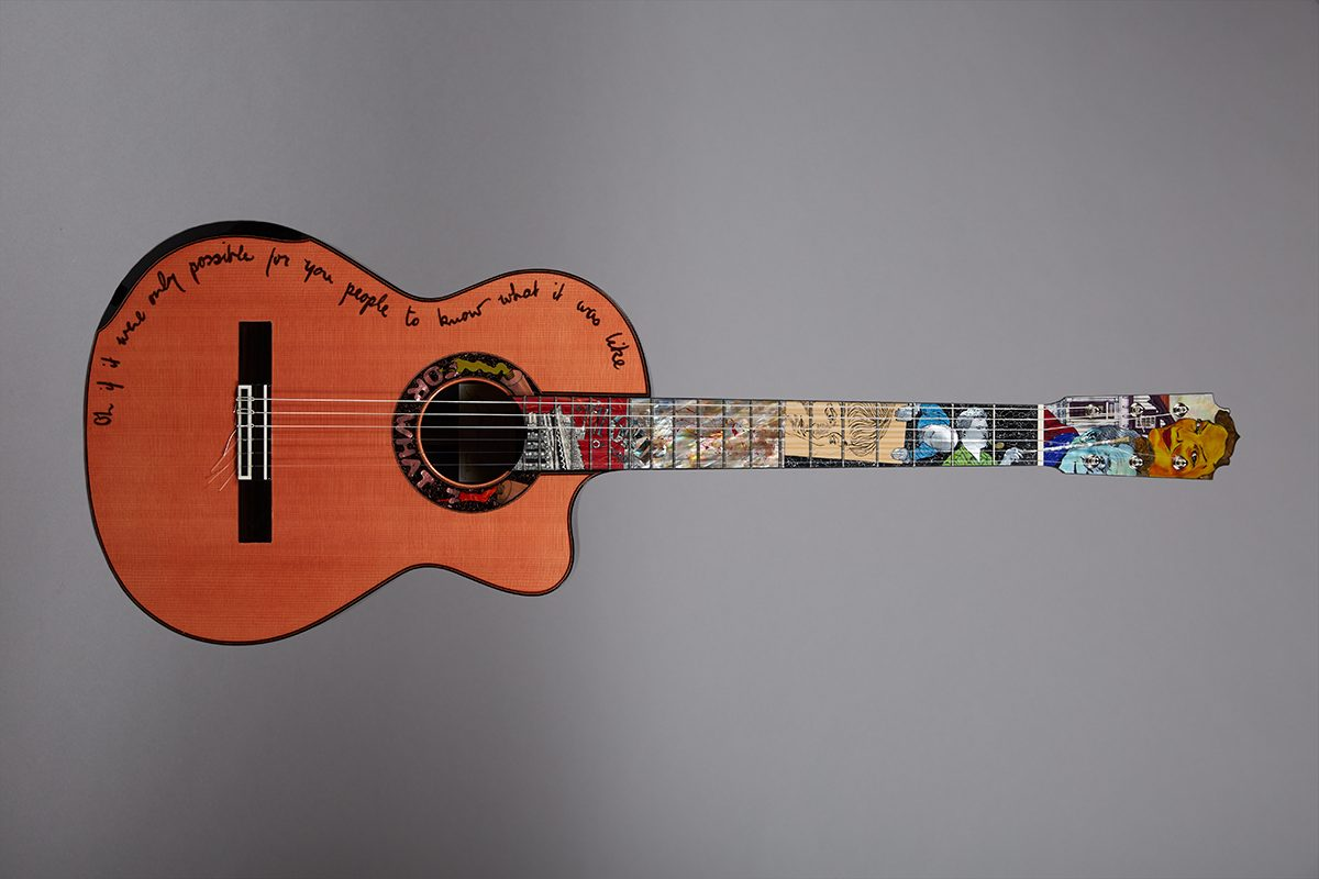 photograph of guitar with detailed inlay on fingerboard and writing around the edge of top half of the body