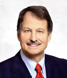 Head shot of man with dark hair and moustache in suit