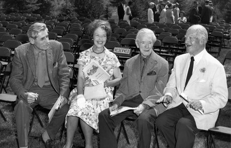Photograph in black and white of three men and one woman sitting down. They are all smiling. There are many empty chairs behind them and a group of people standing and sitting in the background.