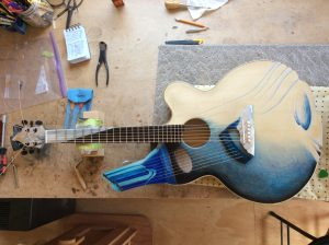 Photograph of a guitar on a work bench seen from above. The guitar is lying on a piece of grey carpet with the headstock to the left. It is decorated in an abstract way in shades of blue, black and cream. There is a secondary partial neck with painted strings coming from the guitar body at a 45 degree angle. There are guitar makers tools on the bench.