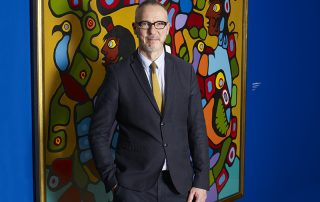 Photo of man in dark suit standing in front of colourful painting.
