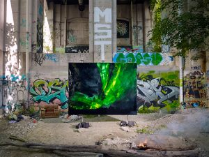 A photograph of a painting within an urban landscape. Graffiti tags cover a cement structure. Tree on right side with shadow of same tree on opposite side. Small fire in foreground. Painting in middle ground of photograph depicting night sky with green northern lights and a tree in centre.