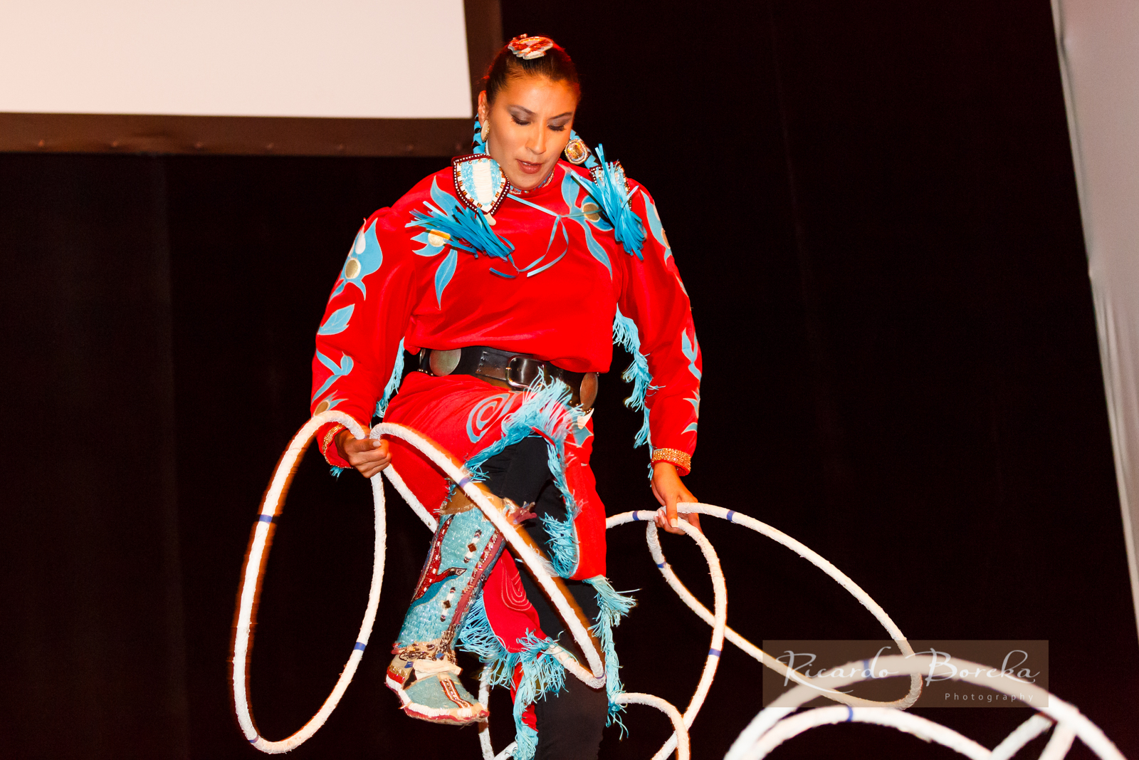 photograph of first nations woman dancing with hoops, wearing a red and blue costume