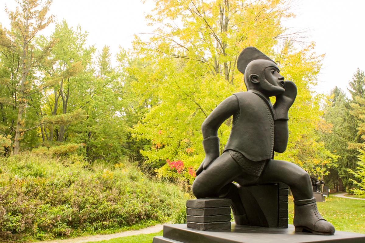 black sculpture of masculine figure in woodland