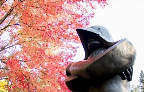 black sculptured figure with autumn leaves on trees