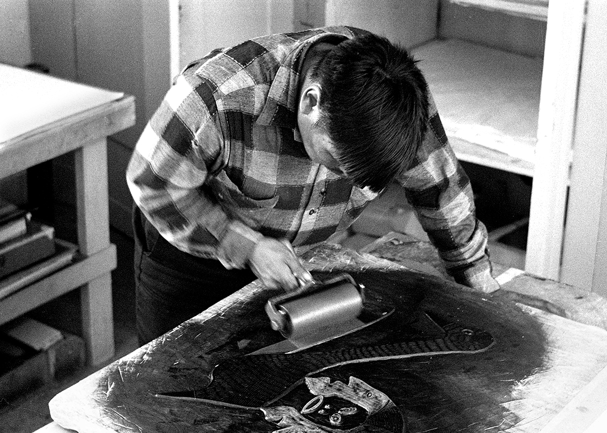 Photograph in black and white of a man with short dark hair wearing a check shirt. He is leaning over a work bench. His left hand is on the bench and in his right hand is an ink roller. He is rolling it on a canvas with the image of a face on it.