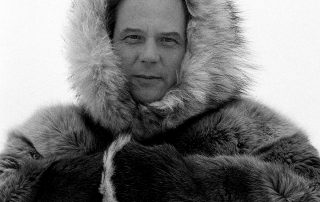 Photograph in black and white of a man looking into the camera. He is wearing a fur coat with the hood up. His arms are across his body with hands concealed in the fur sleeves.