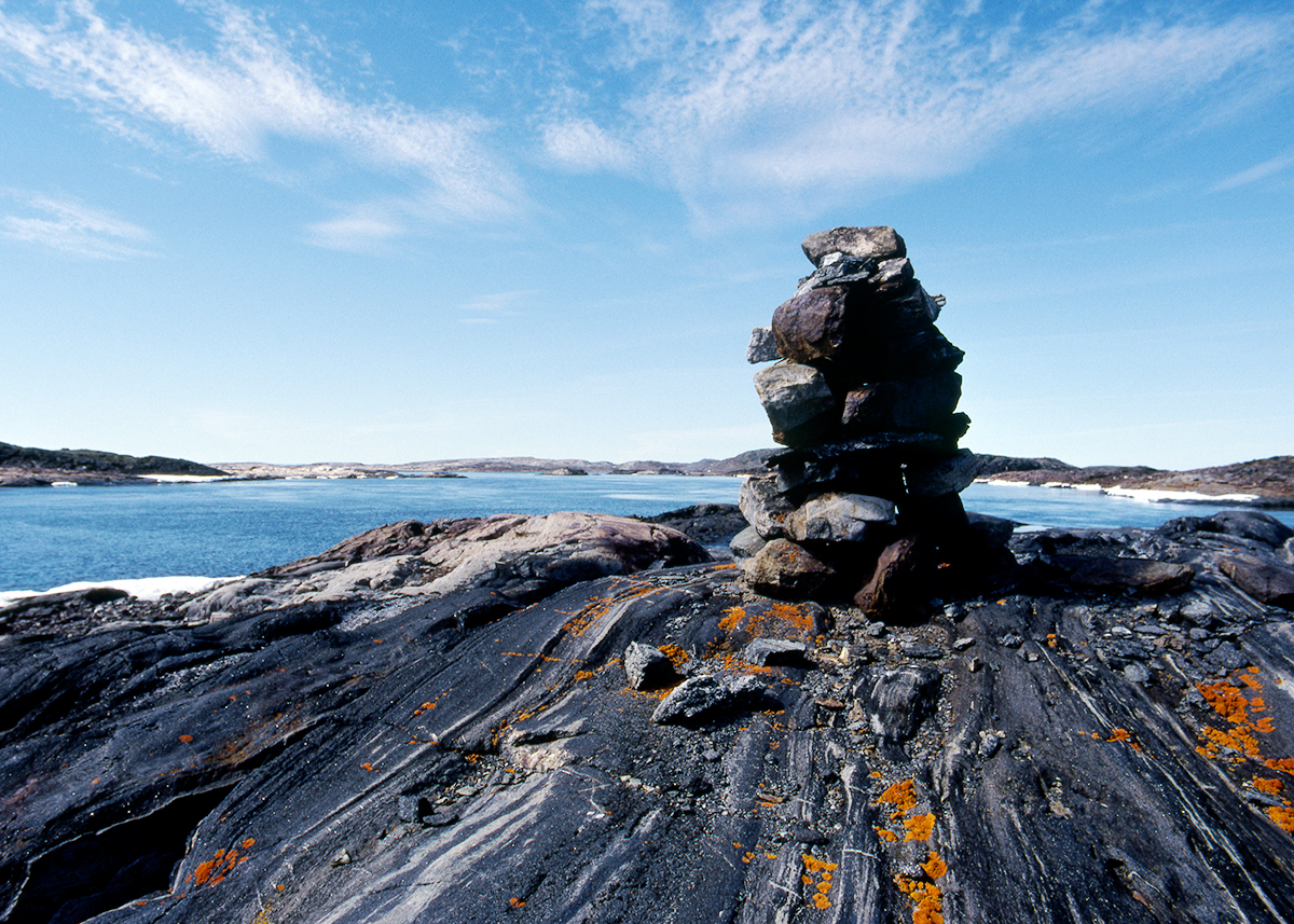Photograph of a pile of rocks (Inuksuk) on dark grey rock with orange lichens. Body of blue water in middle of photograph with rocky land on the horizon and pale blue sky above.