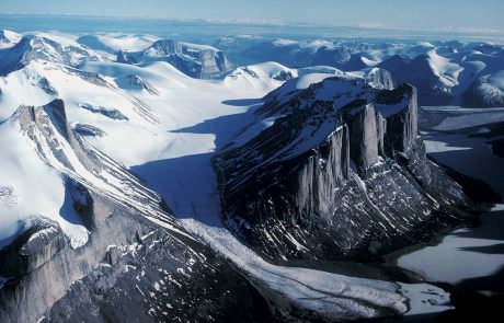 Aerial photograph of snow-covered mountains with body of water in the far distance and blue sky above.