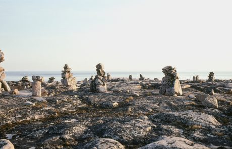 Photograph of rocky landscape with body of water beyond and the sky above. Many piles of stones in various sizes are on the grey rocky land. Moss and lichens are growing on the rocks.