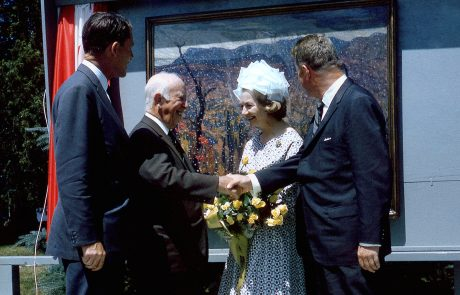 Colour photograph of three men and one woman standing in front of a landscape painting in an impressionistic style. Two of the men are shaking hands. The woman is wearing a dress and hat and holding a bouquet of yellow roses. The men are wearing suits and two of them are looking behind them at the painting.