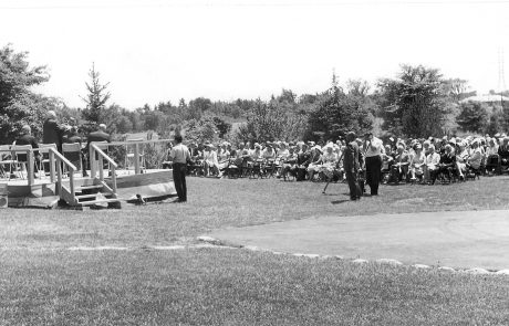 Black and white photograph of a people sitting in chairs on a lawn. There is a platform with people seated in chairs on the left side of the photograph. There are trees in the background.