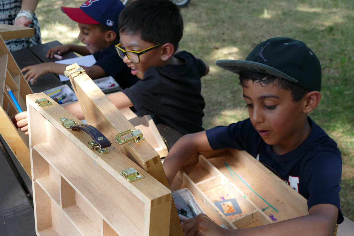children sitting at a table in the outdoors with wooden boxes in front of them