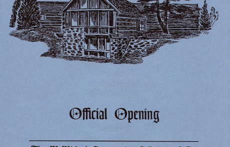 Image of the cover of the programme of the official opening of the McMIchael Canadian Art Collection. Image of log and stone building with trees at each side. The cover is blue with black printing.
