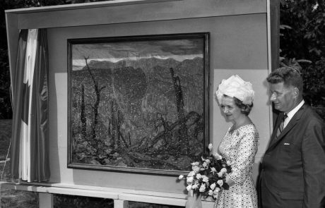 Photograph in black and white of a man and woman standing beside a painting of a landscape in an impressionistic style. The woman is holding a bouquet of roses and wearing a patterned dress and a hat. The man is wearing a suit and tie. There is a curtain pulled aside to the left of the painting.