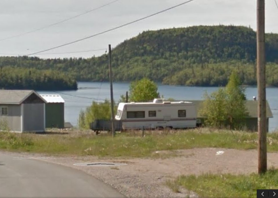photograph of a trailer and small buildings with lake and wooded hillsides in background