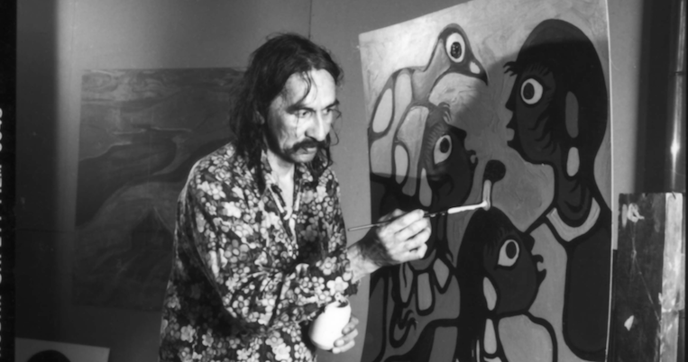 black and white photograph of man painting on a canvas