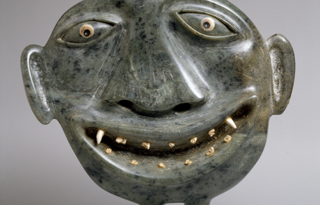 Stone sculpture of a smiling face with tiny legs and protruding ears. There are thirteen teeth in the open mouth.