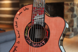 Photograph of mid-section of a guitar. The fretboard is decorated with image of a building. There are words written in black script on the left side of the light orange sounding board and words in capitals and images in a ring around the sound hole.