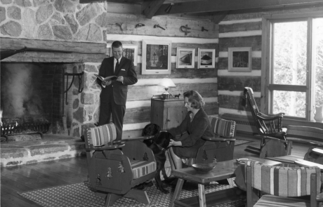 Photograph in black and white of a man and woman in a sitting room.The man is standing by an open stone fireplace reading a book. There is a fire in the hearth. The woman is seated on one of a number of chairs. She is petting a black dog. There are five paintings behind them on log and plaster walls and a window with view of trees to the right.