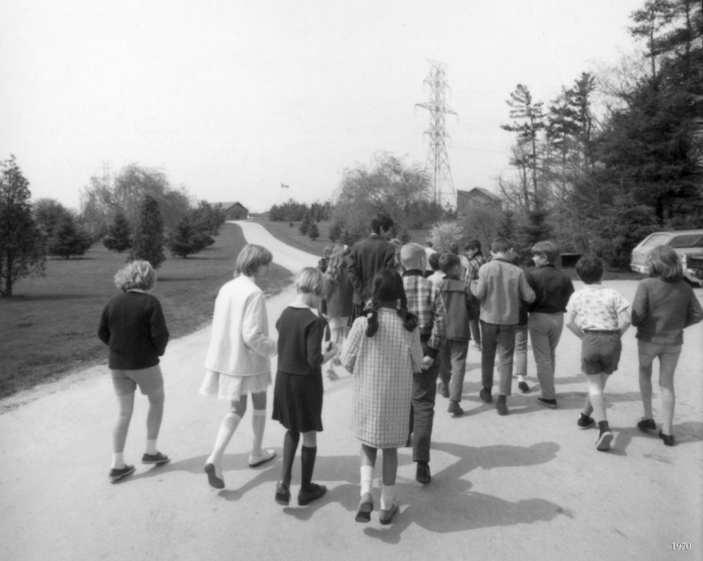 Photograph in black and white of rear view of twenty or so children and one adult walking down a long driveway. There is grass and trees on either side of the driveway.