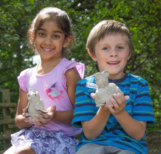 photograph of a girl and a boy each holding a clay animal