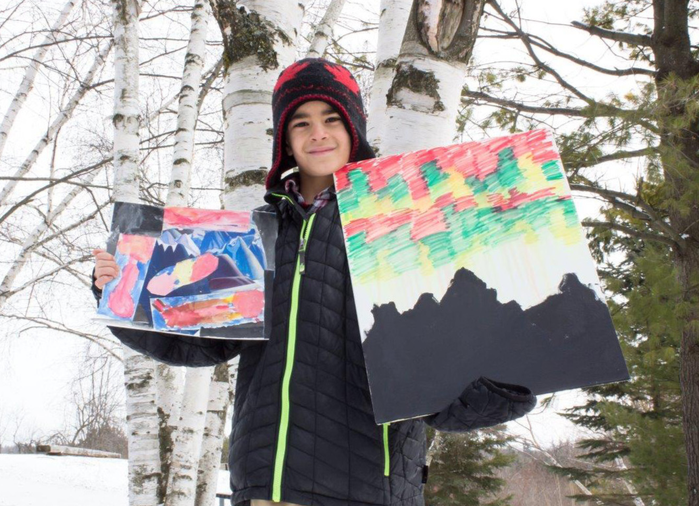 photograph of boy in winter woodland setting holding two paintings