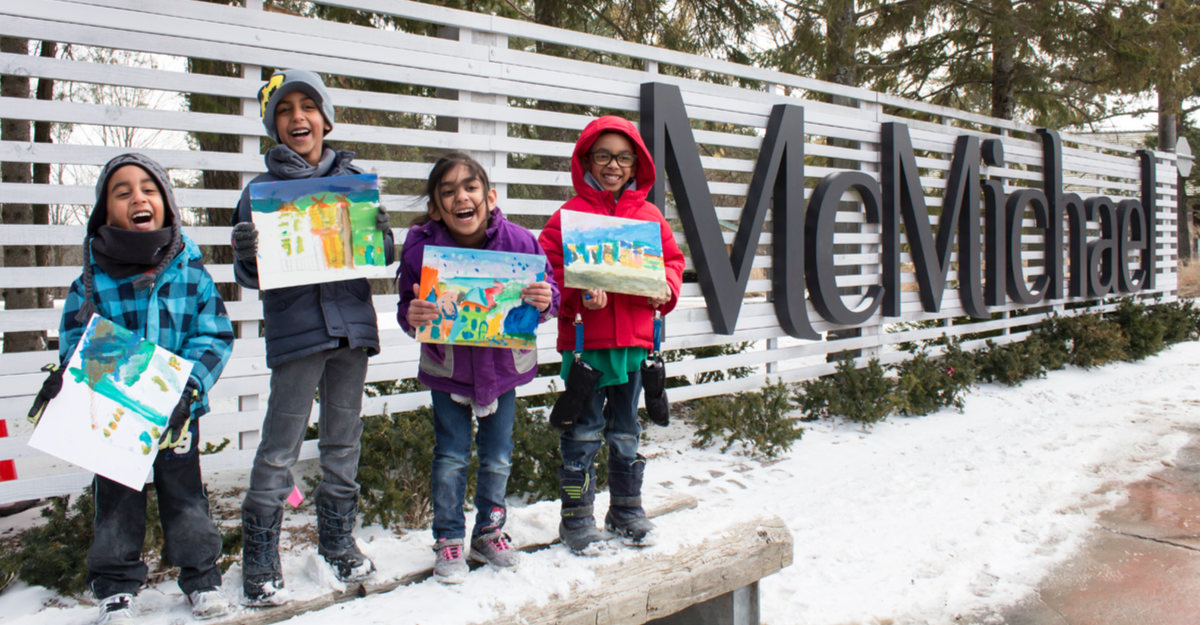 photograph of children in the snow each holding a painting with McMichael sign in background