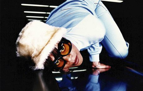 photograph of woman wearing glasses and a fur hat in a contorted position