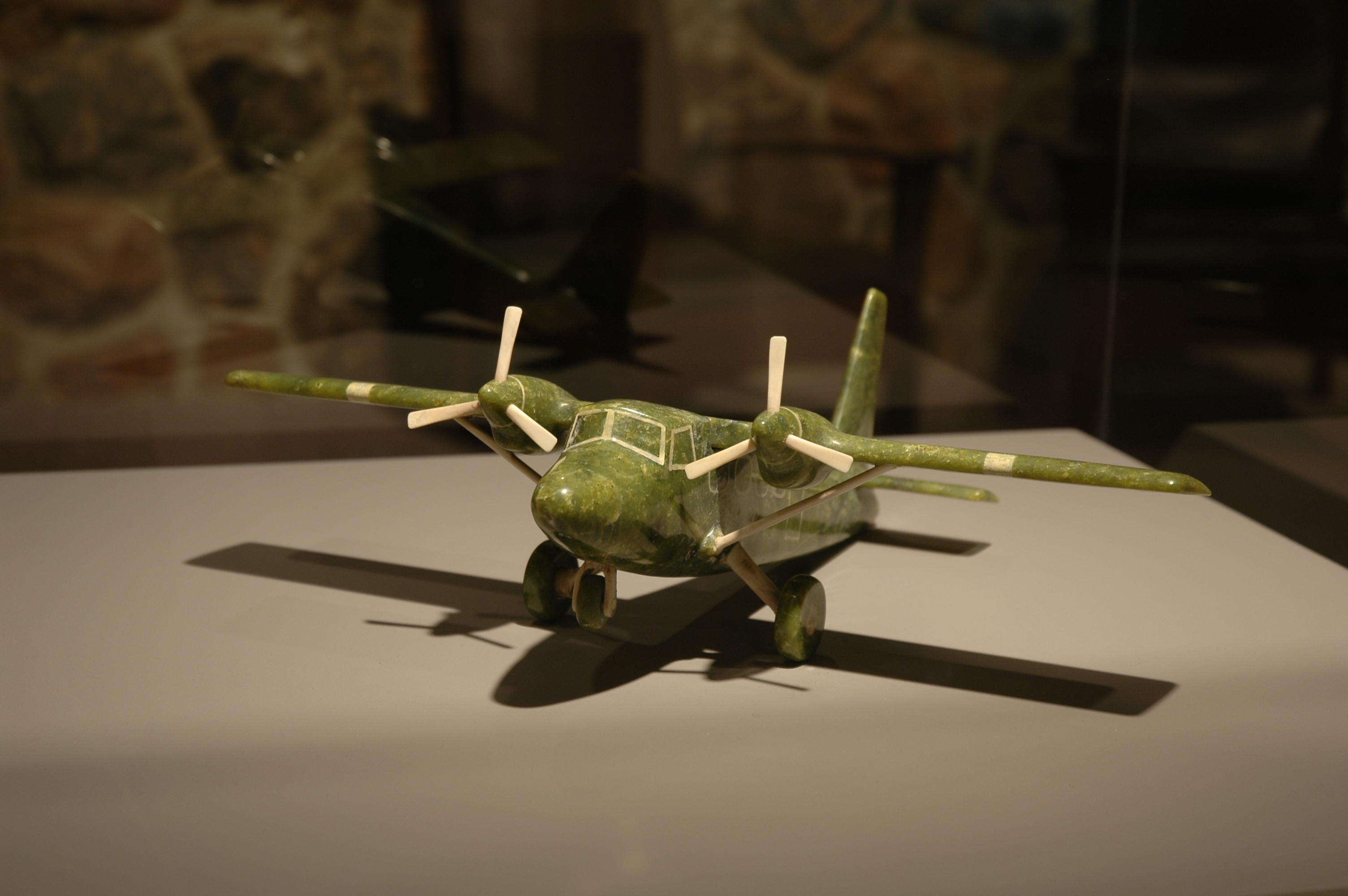 green stone carving of a twin engine airplane