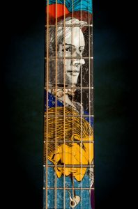 photo pf the neck of a guitar with the image of a man inlaid in the wood