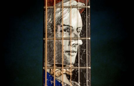 photo of the neck of a guitar with image of man inlaid in the wood