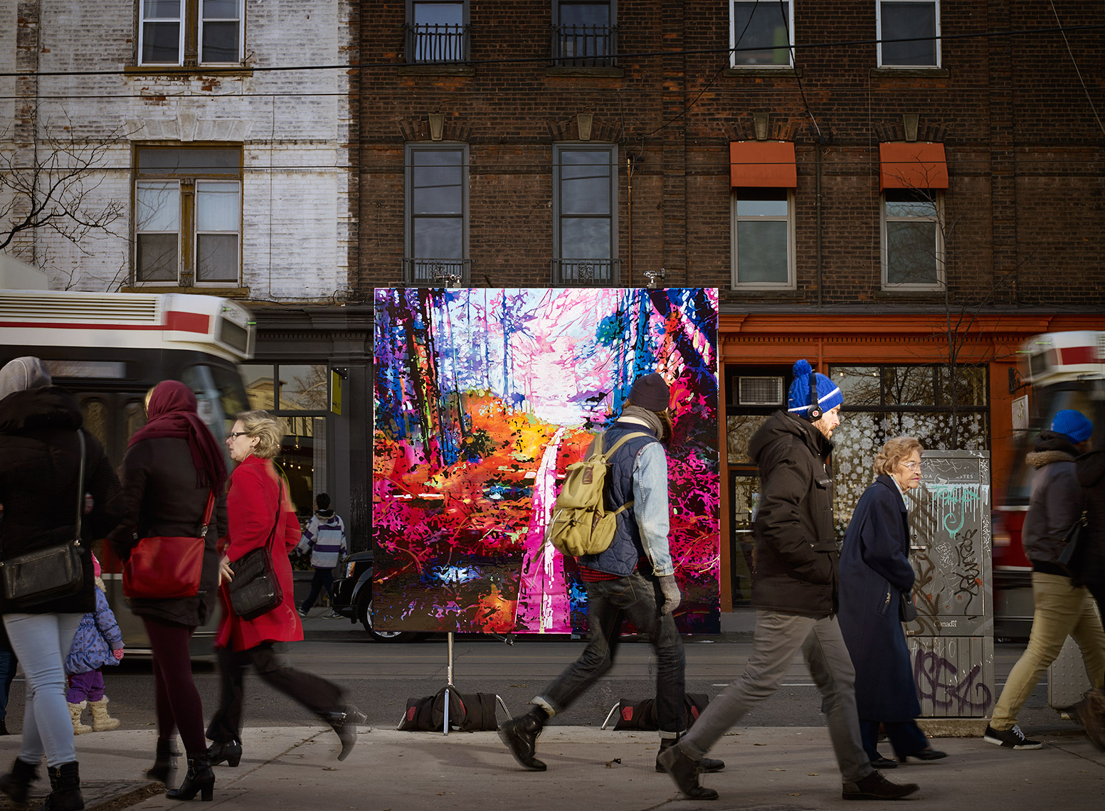 photograph of a landscape painting on a stand in a city street. People walking by on sidewalk and a streetcar