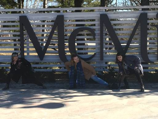 photo of three women in front of McMichael sign