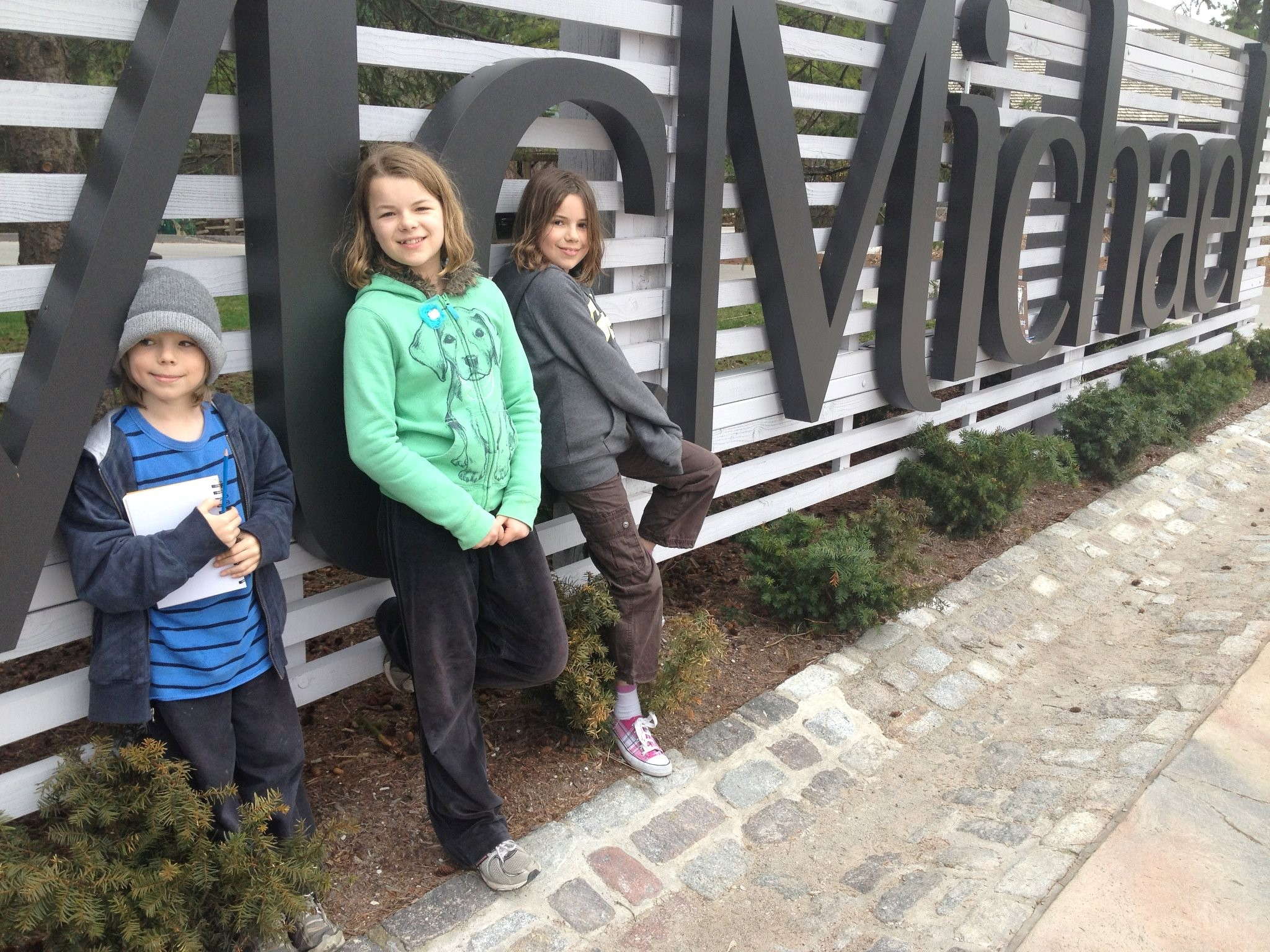 photo of three children in front of McMIchael sign