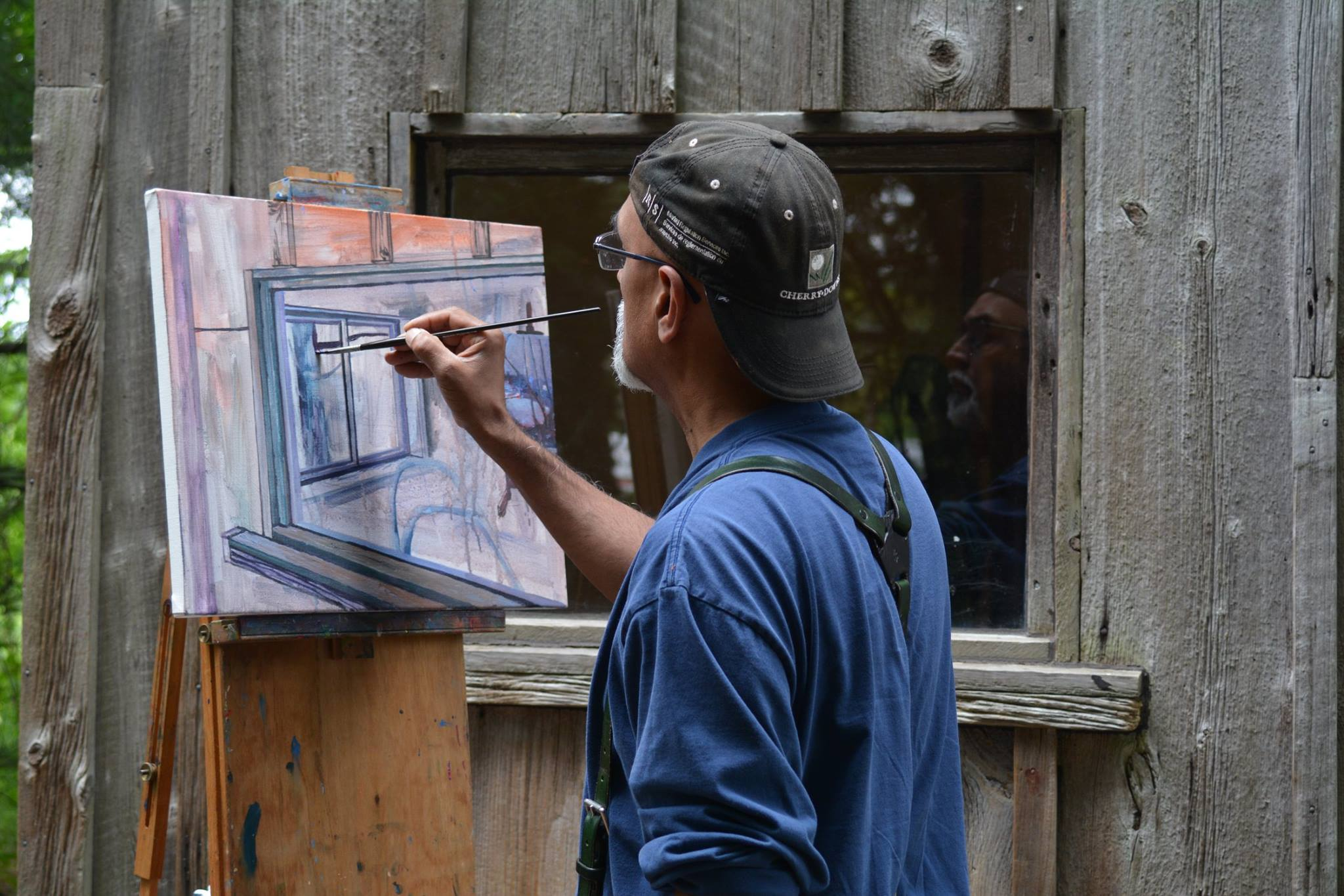 photograph of man painting at an easel.