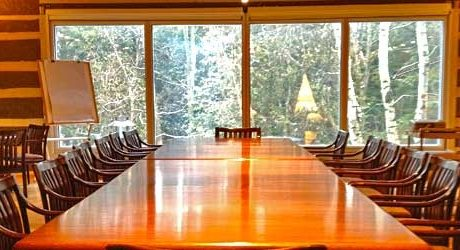 photograph of a long wooded table and chairs with large window behind overlooking snowy trees