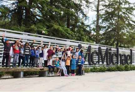 Children in front of McMichael sign in grounds