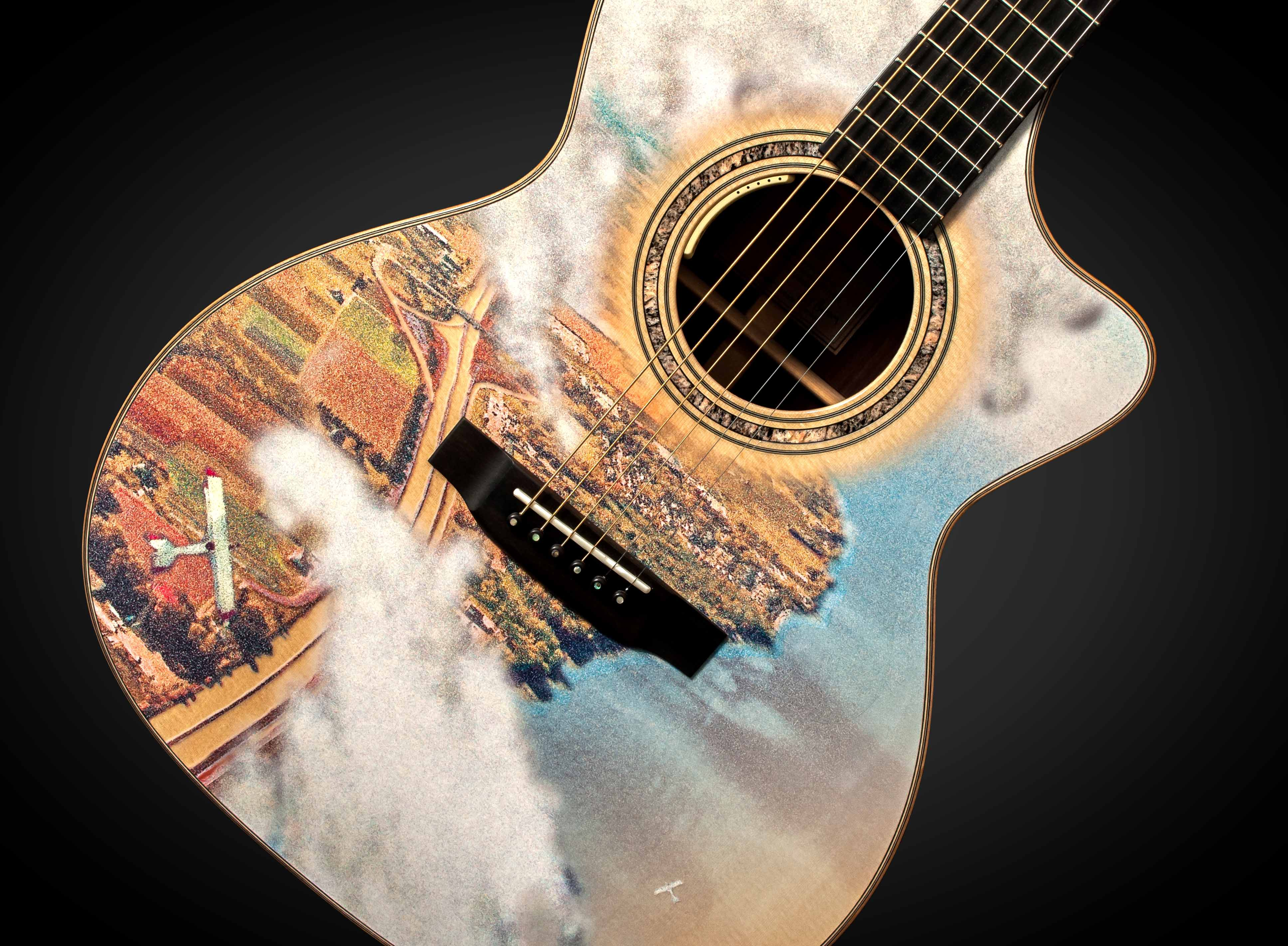 Photograph of the front of a guitar body. The body has an aerial view of a landscape looking down through clouds. There are two small white aeroplanes flying over a patchwork of fields on the left, a highway and a town which borders a shoreline on the right. The body of water is shades of blue.