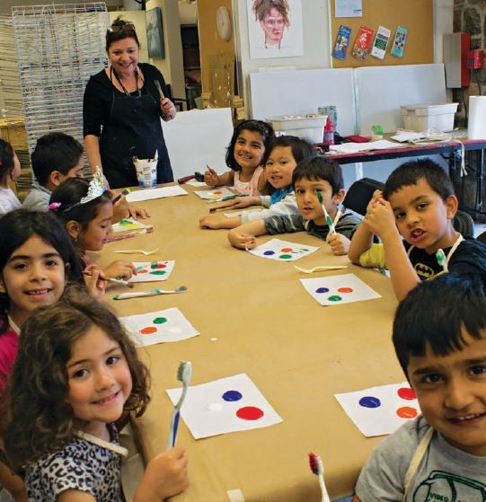 photograph of children sitting around a table with artwork and teacher standing