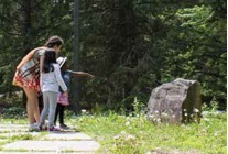 photograph of woman and two children in the outdoors looking at a rock