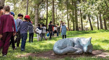 group of children walking in a wooded setting. Sculpture of sleeping fox in foreground