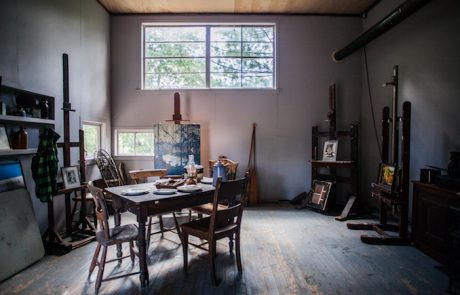 photograph of the interior of a room with window; table, chairs and artwork on easels