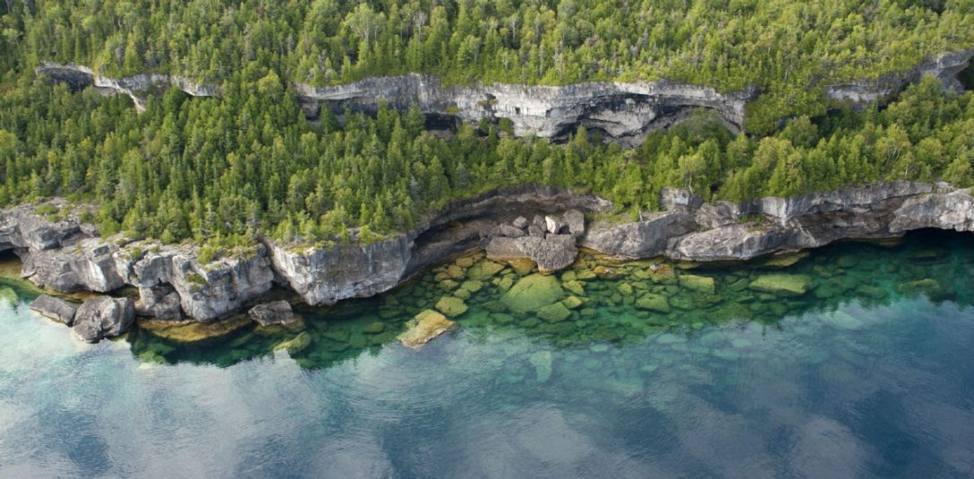 aerial photograph of a rocky shoreline with woods and cliffs above