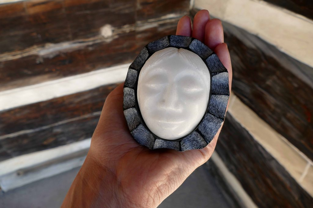 photograph of a hand holding a white stone sculpture of a face with dark grey surround