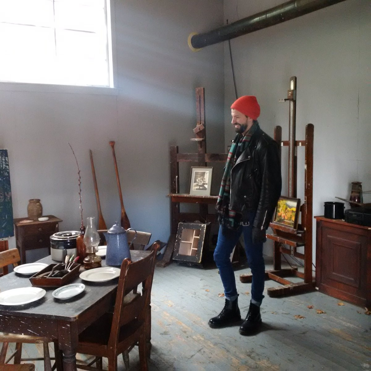 photo of man wearing a red hat in an artist's studio. Light from upper window streaming in